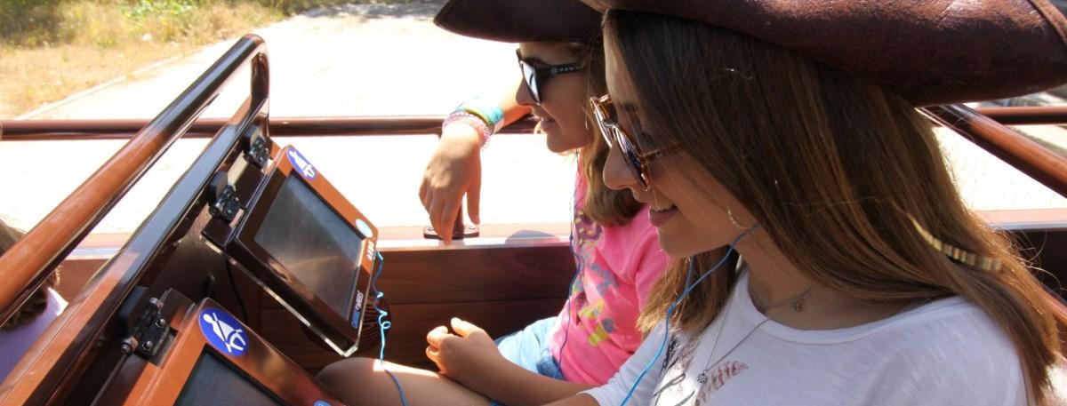 Passageiros em Lisboa autocarro caravela raparigas com tablets interativos a explorarem a história de Lisboa.