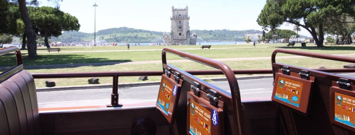Passeio interativo no autocarro turistico caravela. Torre de Belém e tablets em primeiro plano.